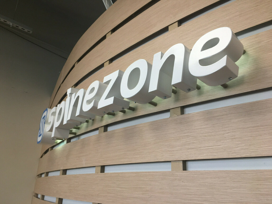Curved wall with logo that reads Spinezone